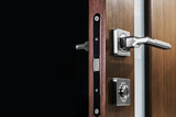 door handle and latch of brass on veneer doors. place for your text on a black background - 187572913