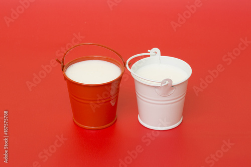 Red and white buckets with milk on a red background