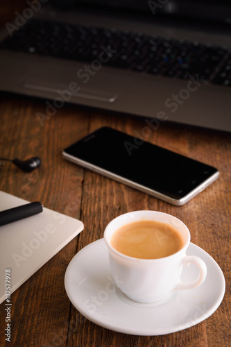 Laptop (notebook) mobile phone (smartphone) and notepad with pen on old wooden table. Work place modern.Cup of coffee