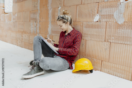 young, pretty, blonde woman with yellow helmet is planning on the notebook and tablet the expansion of her loft - 187579372