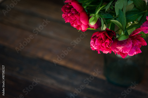 Foto Murales Beautiful  bunch of peony on a wooden table. Spring or summer lovely bouquet. Card, text place, copy space. Wallpaper, trendy color.