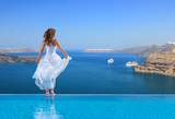 Bride standing on the edge on the infinity pool