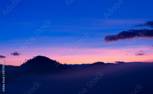 Foto op Plexiglas Donkerblauw Beautiful orange light on mist mountain of fog when sunrise time. Mountain landscape in the north of Thailand