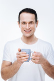 Delicious drink. Cheerful positive nice man holding a cup of tea and smiling while looking at you - 187592955