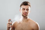 Portrait of a handsome half naked man spraying perfume - 187594517