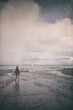 Girl walking on the shore, dramatic sky