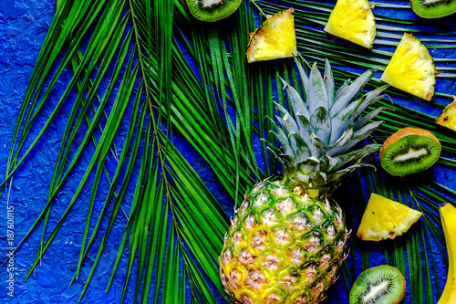 Foto Murales Concept of summer tropical fruits. Kiwi, pineapple and palm bran