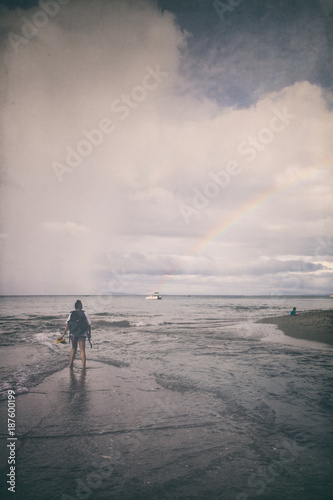 Girl walking on the shore, dramatic sky - 187600199