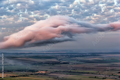 Aerial view over a beautiful rural scene with green fields and trees  and beautiful white and pink clouds, Dobrogea , Romania - 187604319