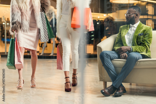 stylish african american man looking at fashionable girls walking with shopping bags in mall