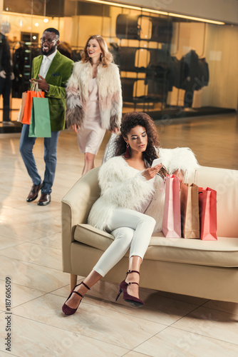 young woman using smartphone while sitting with shopping bags and stylish couple walking behind in mall