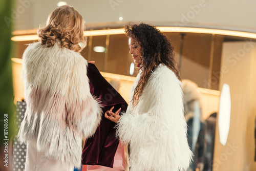 fashionable multiethnic women in fur coats shopping together in mall