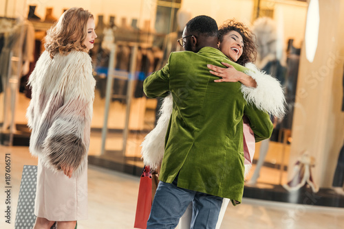 fashionable young african american couple hugging while shopping in mall