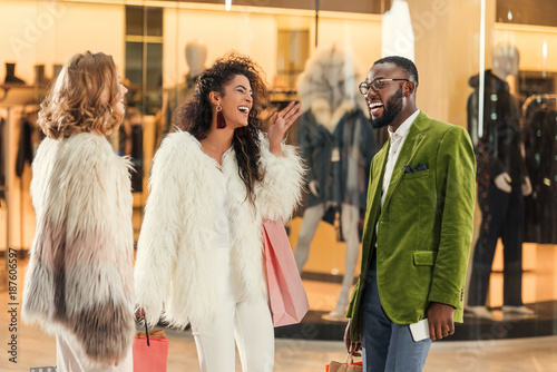 cheerful stylish multiethnic people talking while shopping together in mall