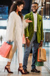 smiling young stylish african american couple with shopping bags walking together in mall