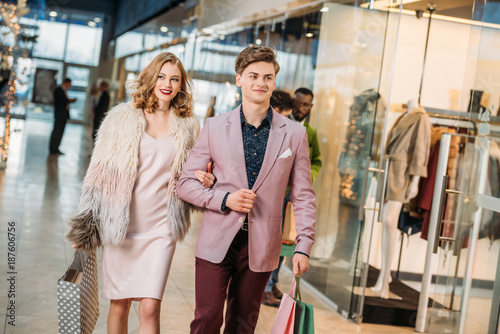 happy stylish young couple with shopping bags walking together in mall
