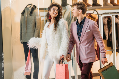 stylish young multiethnic couple with shopping bags walking together in mall