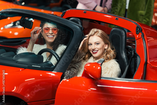 fashionable smiling multiethnic women sitting in luxury red car and looking at camera