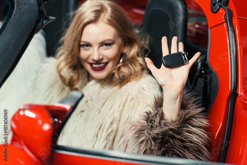 close-up view of fashionable young woman holding car key and looking at camera while sitting in luxury luxury car