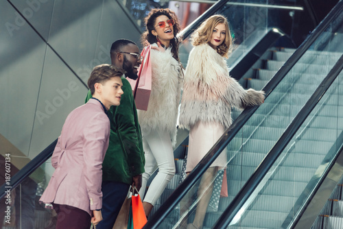 stylish multiethnic young shoppers on escalator at mall with packages