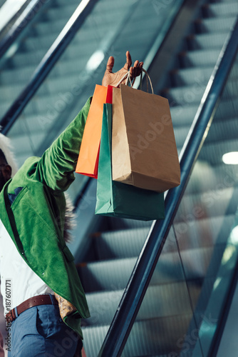 cropped shot of man holding shopping bags while riding escalator at mall