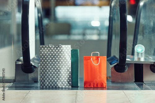 shopping bags in front of escalator at shopping mall