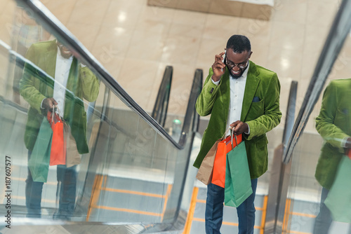 smiling stylish man with shopping bag talking by phone on escalator at mall