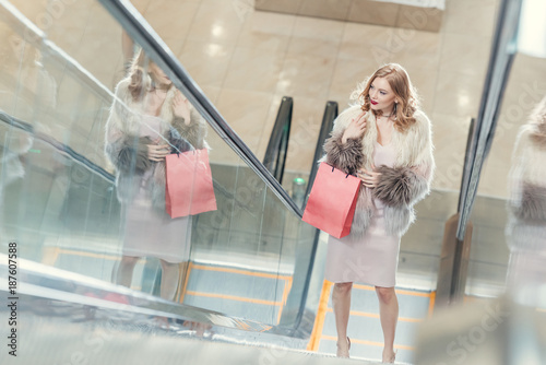 high angle view of stylish women with shopping bag on escalator at mall