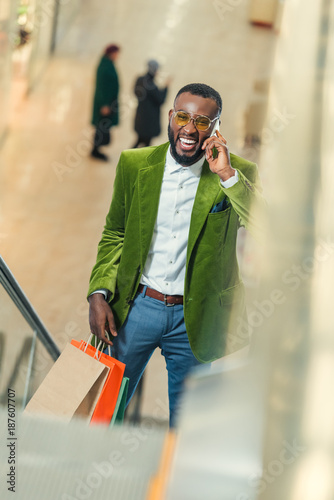 happy stylish man on escalator at shopping mall and talking by phone