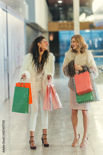 stylish women in fur coats with shopping bags walking by mall and laughing