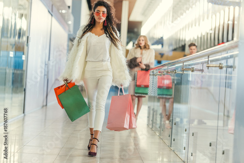 stylish young woman in fur coat with shopping bags walking by mall