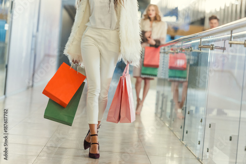 cropped shot of stylish woman with paper bags walking by shopping mall