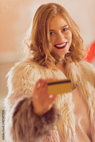 beautiful young woman in fur coat with golden credit card on shopping