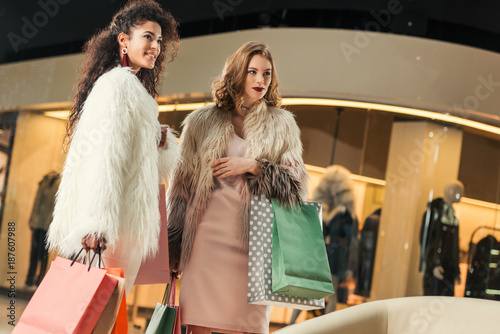 beautiful young multiethnic women in trendy fur coats holding paper bags while shopping together in mall