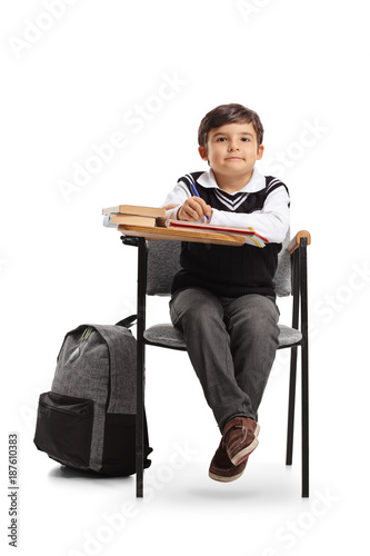 Little schoolboy sitting in a school chair