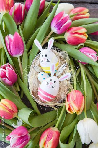 Leinwanddruck Bild Buntes Osternest mit Tulpen