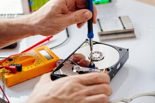 Technician repairing broken hard disk drive.