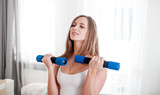 Sporty young woman exercising at home with dumbbells - 187620323