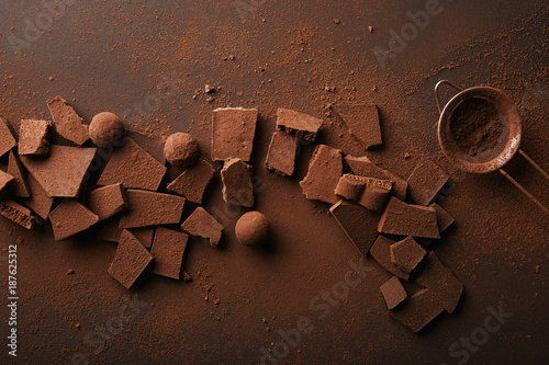 Foto Murales top view of arrangement of various types of chocolate, truffles and sieve with cocoa powder