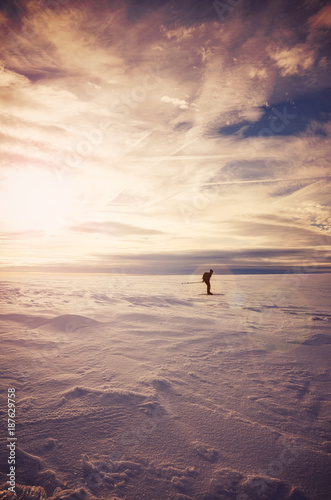 Foto op Plexiglas Cappuccino Winter mountain landscape with cross-country skier silhouette at sunset, lens flare effect, color toned picture, Karkonosze National Park, Poland.