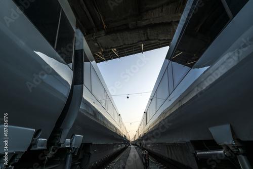 Fototapeta Wiev between two passenger trains standing under a bridge