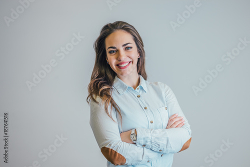 Successful young business woman with hands folded, smiling.