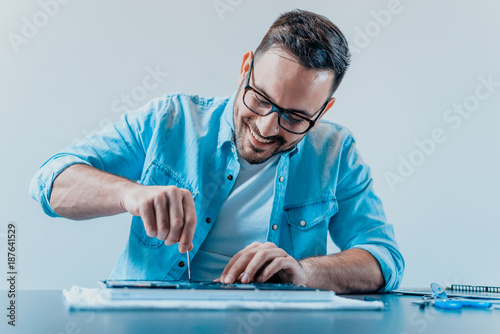 The engineer repairs the laptop