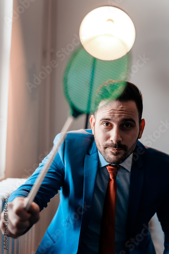 Handsome young businessman with fly swatter. Looking at camera. - 187641565