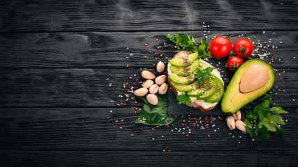 Sandwich with avocado, butter and chia seeds. On a wooden background. Top view. Free space for your text.