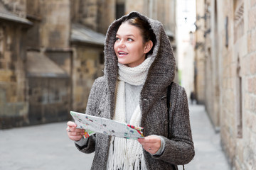 girl teenager in hood holding map