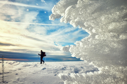 Foto op Canvas Wit Close up picture of ice formations at sunset, cross-country skier silhouette in distance, selective focus.