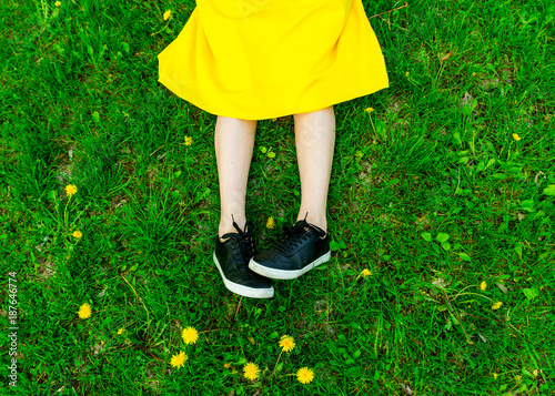 Foto op Plexiglas Gras Above view of incognito woman in yellow skirt sitting on green grass, among flowers, resting. Summertime concept. Rest in park. Colorful and positive mood.