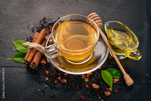 Fototapeta Tea in a cup of cinnamon and honey on a wooden background. Hot drink Top view. Copy space.