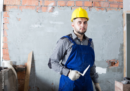 Man builder is ready for plastering the walls © JackF